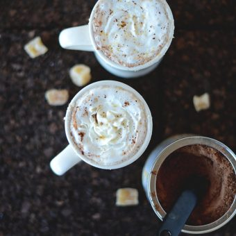 Mugs of our warming Ginger Hot Chocolate recipe alongside cocoa powder and ginger candies