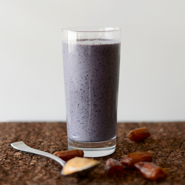 Glass of our Peanut Butter and Jelly Smoothie recipe beside dates and a spoonful of nut butter