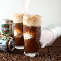 Straws, cans of natural root beer, and two glasses of our Vodka & Coconut Ice Cream Root Beer Floats recipe