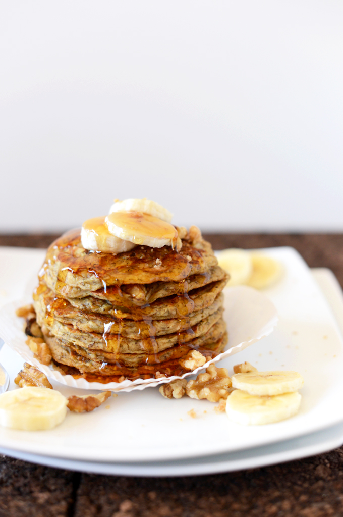 Stack of Banana Nut Muffin Pancakes topped with sliced bananas and syrup