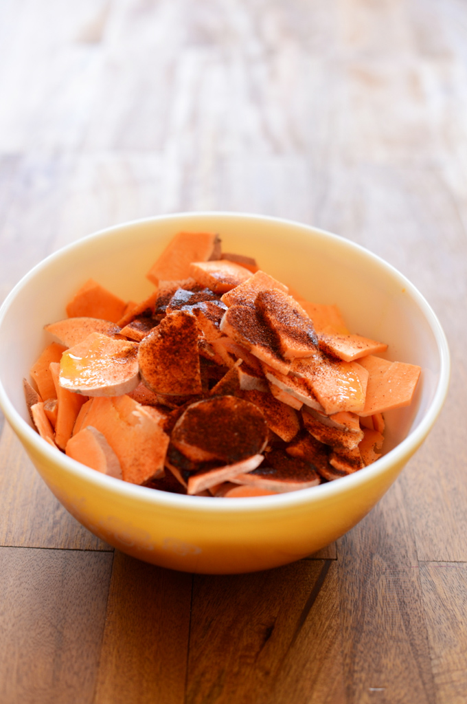 Bowl of sweet potato slices topped with oil and spices for making Chipotle Spiced Sweet Potatoes