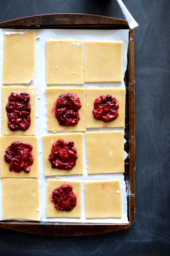 Baking sheet with squares of homemade Pop Tart dough with dollops of mixed berry compote on top