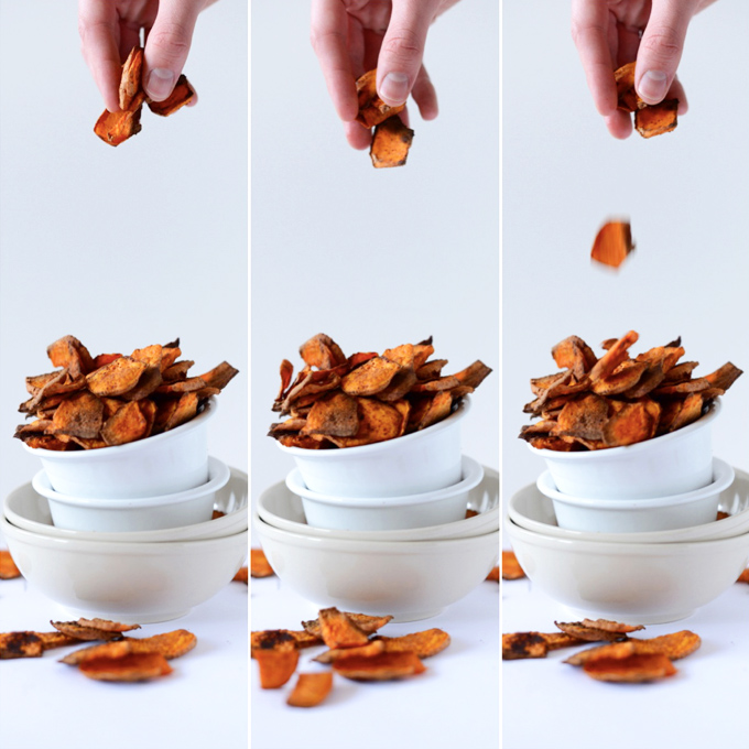 Dropping a handful fo Spicy Sweet Potato Chips into a bowl for a game day snack