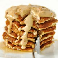 Using a fork to slice into a stack of Peanut Butter Flaxseed Pancakes