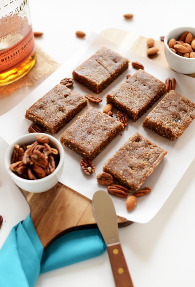 Batch of cut Boozy Pecan Pie Bars on a cutting board surrounded by almonds and pecans