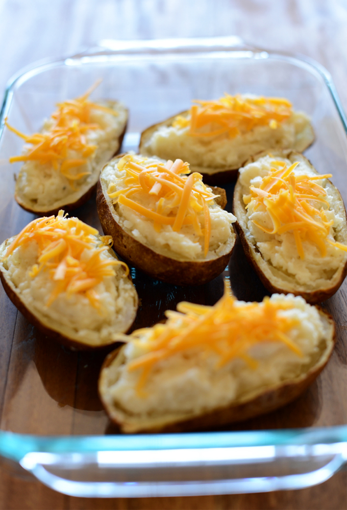 Pan of Cauliflower Twice-Baked Potatoes topped with shredded cheddar cheese