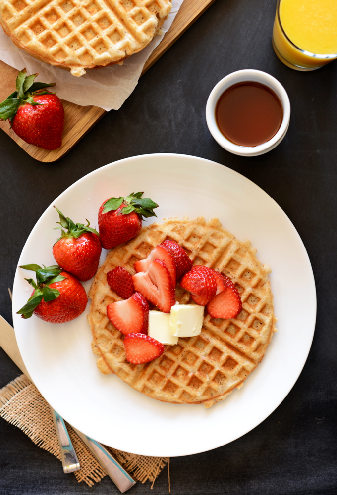 Gluten-Free Oat Waffle topped with fresh strawberries and vegan butter