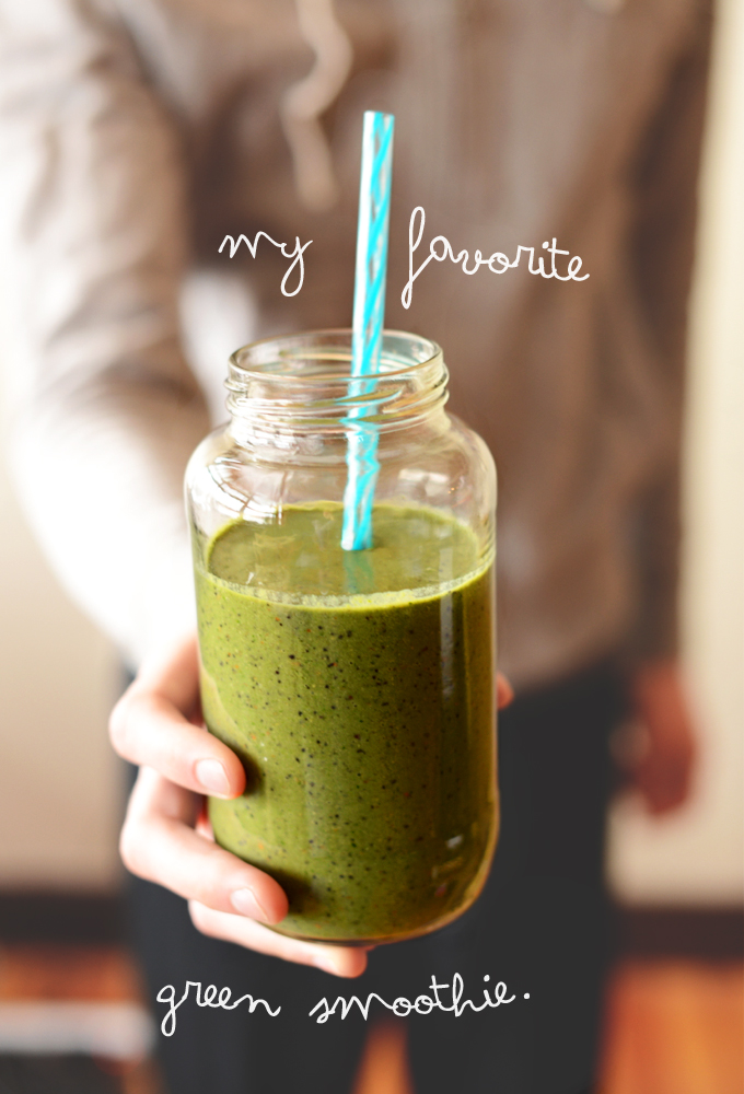 Holding a jar filled with a batch of our Favorite Green Smoothie recipe