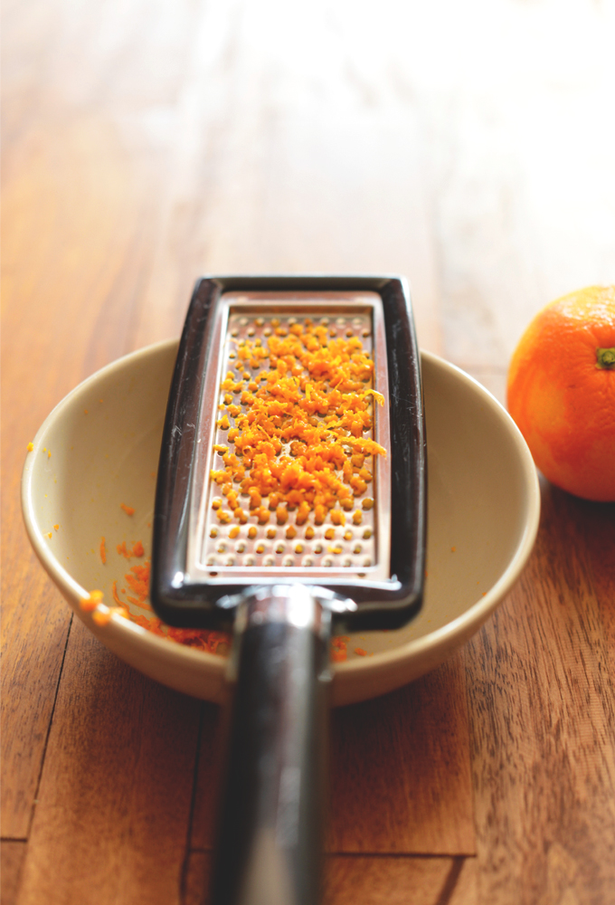 Orange zest grated over a bowl for making simple homemade jam