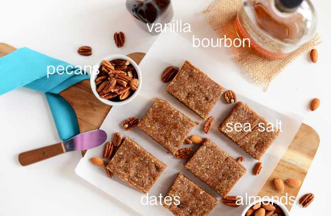Parchment-lined cutting board of Raw Boozy Pecan Pie Bars surrounded by ingredients used to make them