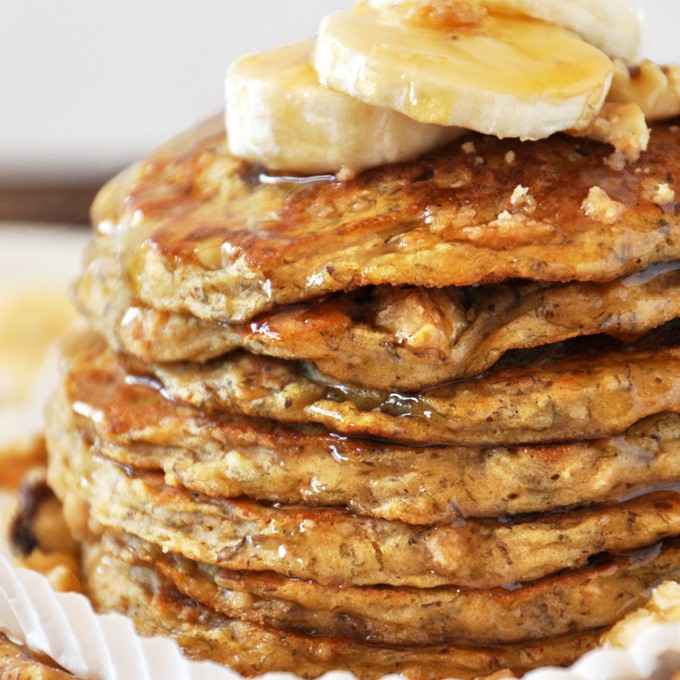 Close up shot of a batch of our Vegan Banana Nut Muffin Pancakes dripping with syrup