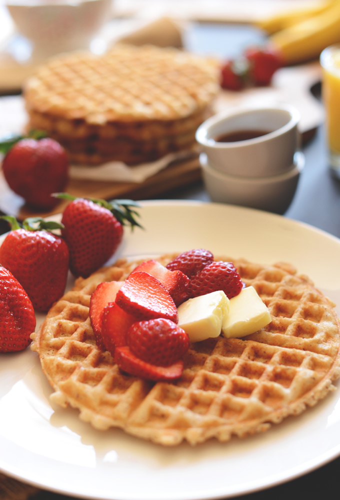Plate with a homemade gluten-free waffle topped with vegan butter and strawberries