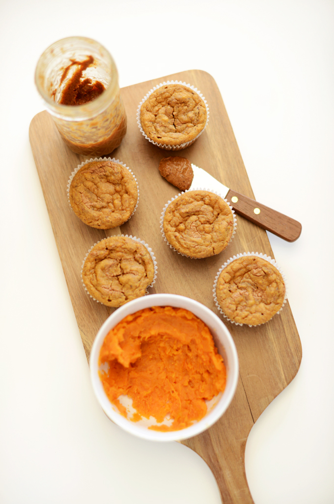 Cutting board with a batch of Vegan Sweet Potato Almond Butter Muffins alongside ingredients used to make them