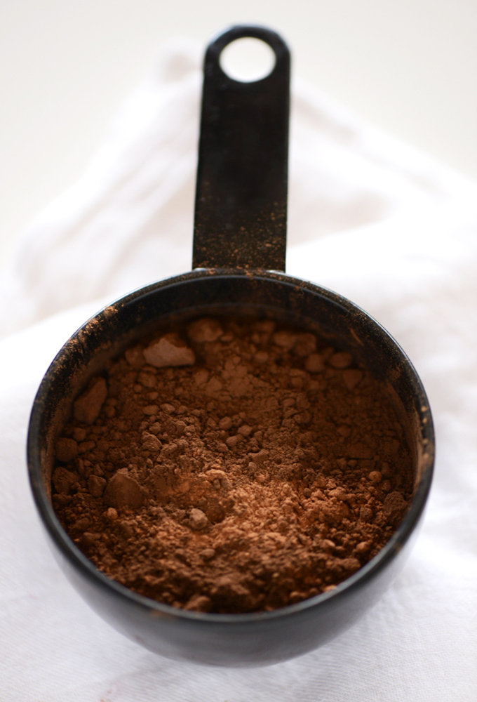 Measuring cup of cocoa powder for making black bean brownies