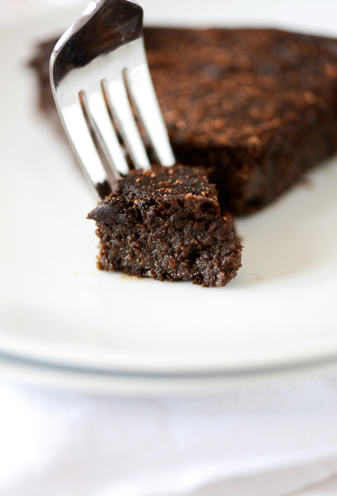 Grabbing a bite of Fudgy Gluten-Free Chocolate Cake from a plate