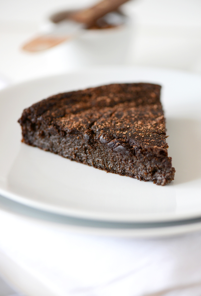 Plate with a slice of Fudgy Gluten-Free Chocolate Cake sprinkled with cocoa powder