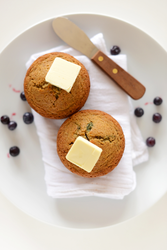 Two Gluten-Free Blueberry Muffins topped with vegan butter