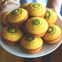 Holding a plate piled high with Gluten-Free Jalapeno Cornbread Muffins