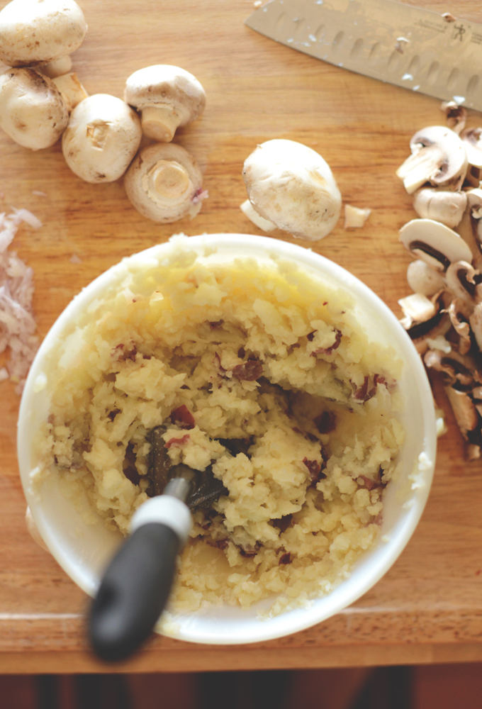 Bowl of cauliflower mashed potatoes surrounded by fresh mushrooms