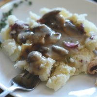 Using a fork to pick up a bite of Cauliflower Mashed Potatoes topped with Mushroom Gravy
