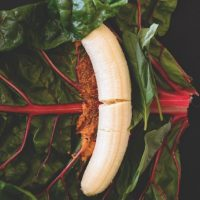 Fresh basil, banana, and peanut butter on a chard leaf