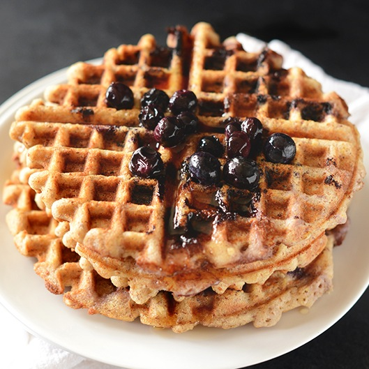 Plate with a stack of two Blueberry Lemon Waffles topped with fresh blueberries