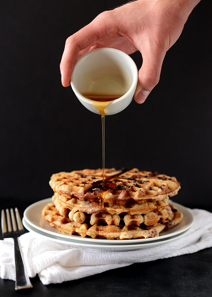 Pouring syrup onto a stack of our GF Vegan Lemon Blueberry Waffle recipe