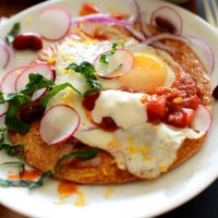 Plate of Gluten-Free Breakfast Tostadas made with kale, radish, egg, and salsa