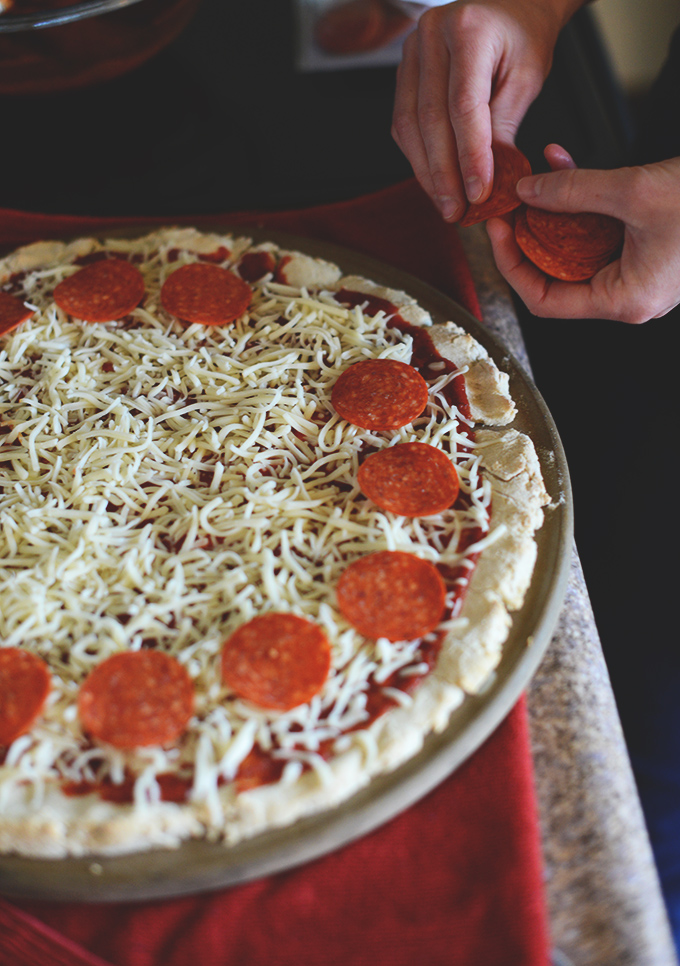 Adding pepperoni slices to a homemade pizza