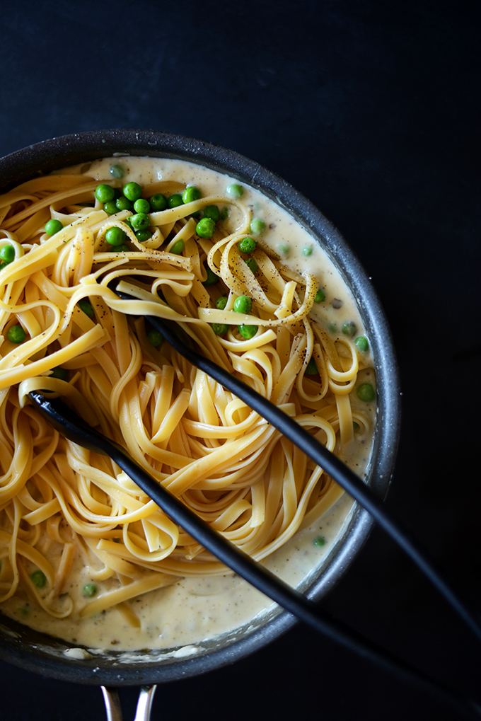 Tongs in a pot of Healthy Alfredo Pasta with Peas