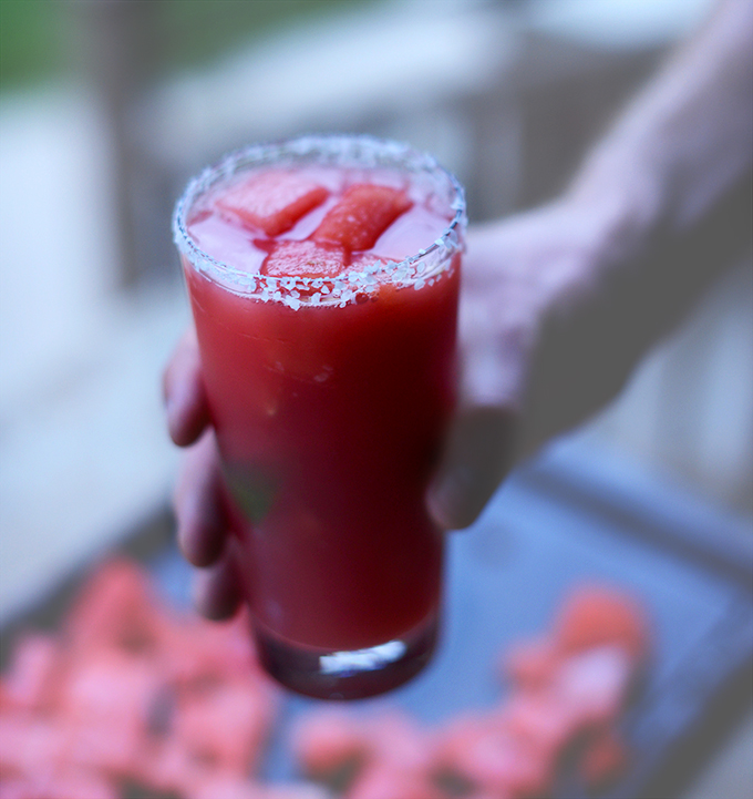 Tall glass of our Lime Watermelon Margarita recipe with chunks of melon in it
