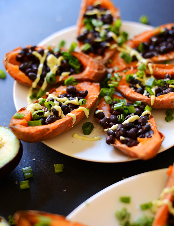 Close up shot of Loaded Black Bean Sweet Potato Boats with green onion and avocado crema