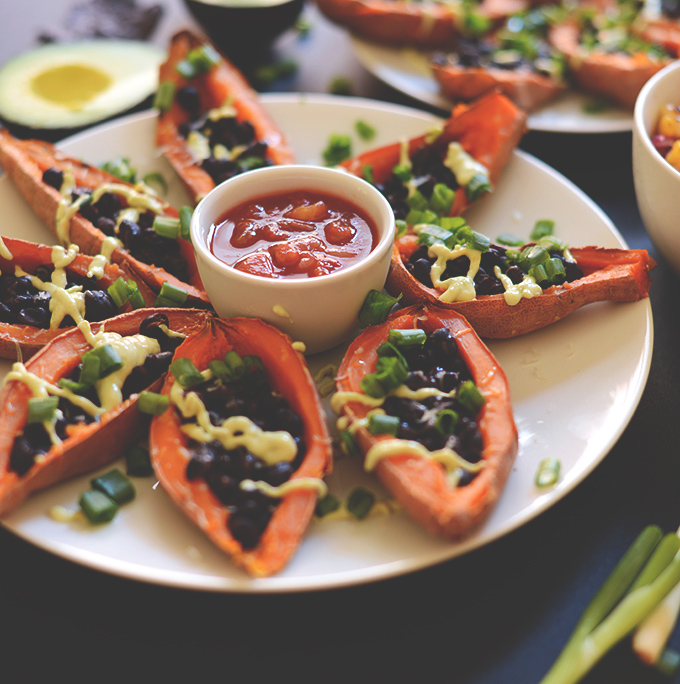 Plate of Loaded Mexican Sweet Potato Boats with a bowl of salsa in the center