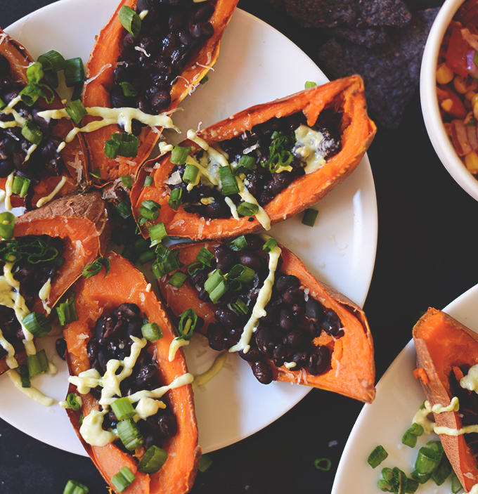 Plate of Loaded Sweet Potato Black Bean Boats drizzled with avocado crema