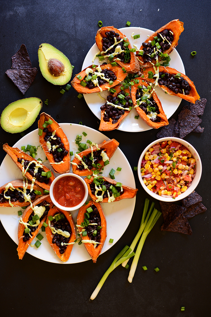 Plates of Sweet Potato Boats loaded with black beans, avocado sauce and more