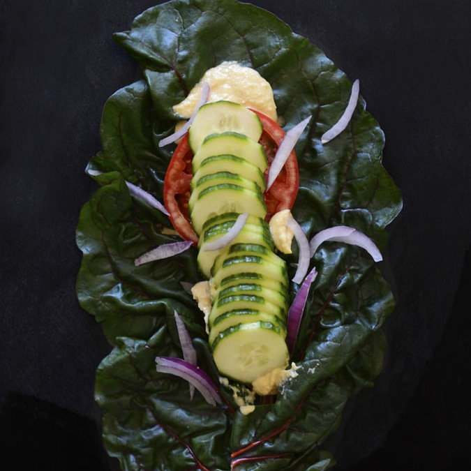 Vegan wrap made with a chard leaf, hummus, and fresh vegetables