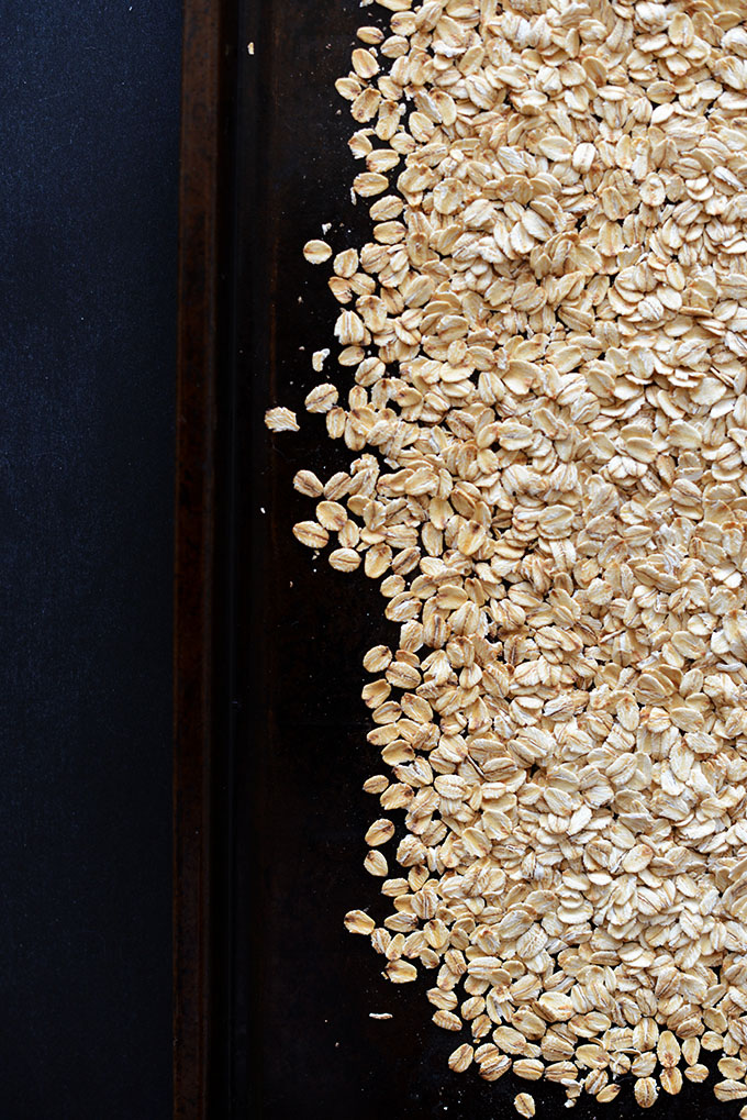 Toasting rolled oats on a baking sheet for homemade granola bars