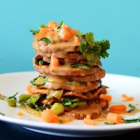 Side view of a stack of Thai Sweet Potatoes drizzled with Peanut Sauce