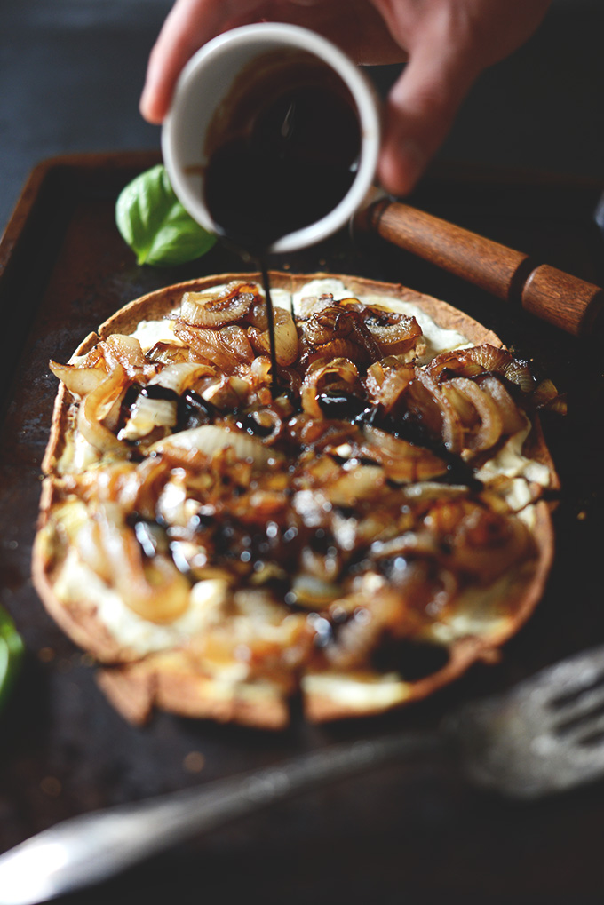 Drizzling balsamic reduction onto our Caramelized Onion and Goat Cheese Pizza