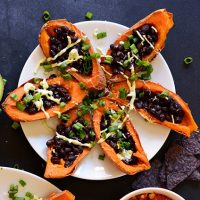 Plate of Sweet Potato Black Bean Boats topped with sliced green onion and avocado crema