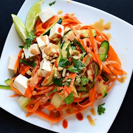 Plate of Noodle-Free Tofu Pad Thai topped with peanut sauce, cilantro, and sriracha