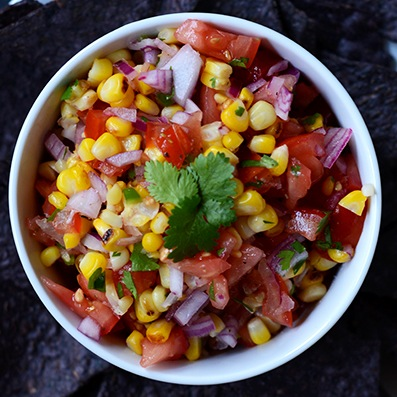 Overhead shot of a big bowl of Grilled Corn Salsa topped with fresh cilantro