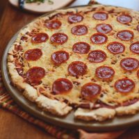 A whole homemade Gluten-Free Pepperoni Pizza on a big plate