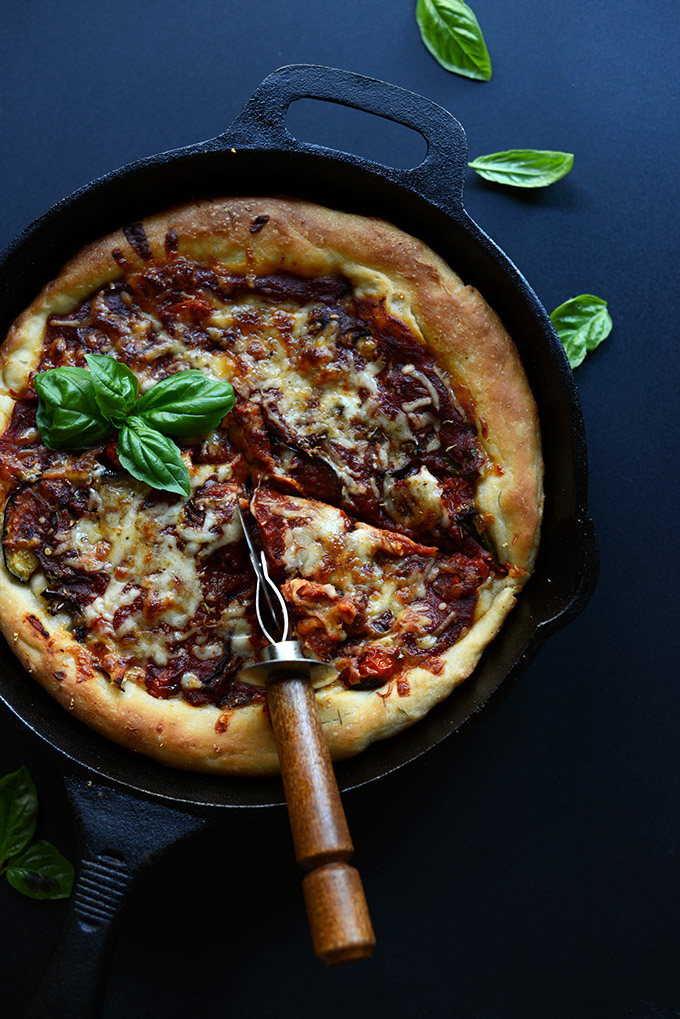 Skillet filled with vegetarian Deep Dish Pizza with fresh basil