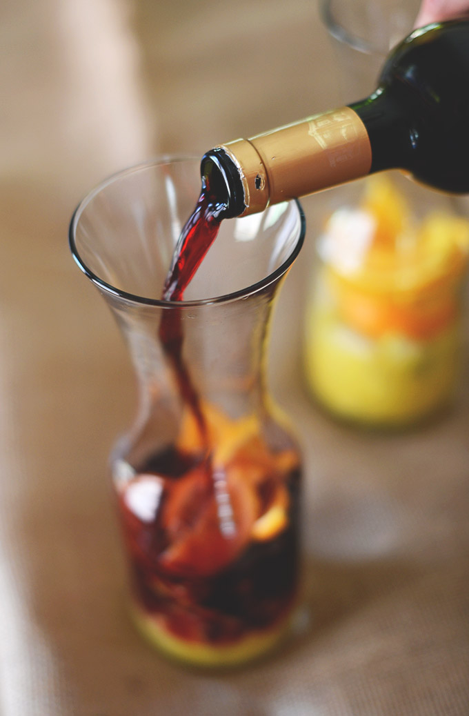 Pouring red wine into a jug for our homemade Sangria recipe
