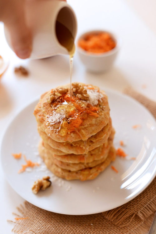 Pouring syrup over a stack of Carrot Coconut Pancakes for a vegan breakfast