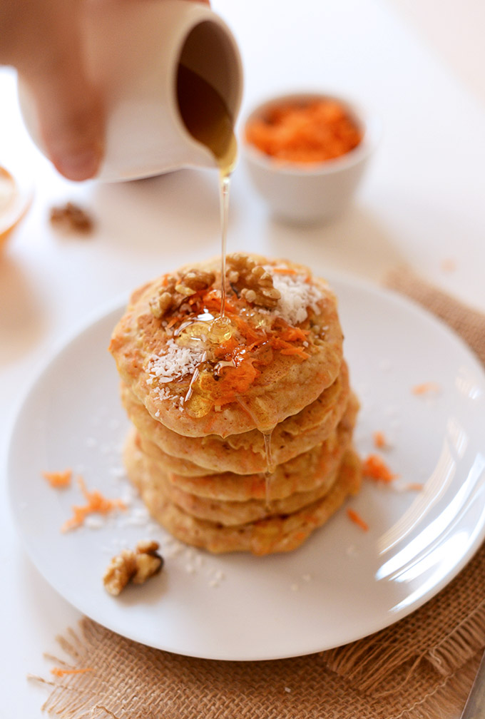 Pouring syrup onto a stack of Carrot Cake Pancakes made with coconut and walnuts
