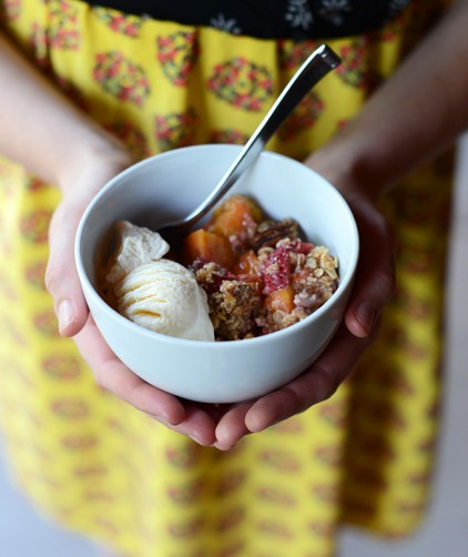 Holding a bowl of our delicious Gluten-Free Summer Fruit Crisp recipe