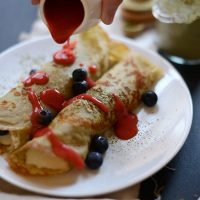Drizzling strawberry sauce onto Gluten-Free Green Tea Crepes