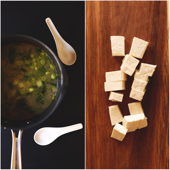 Sauce pan of miso broth and cubes of tofu on a cutting board